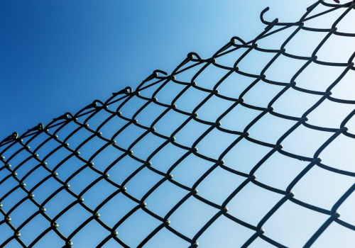This photo shows some new chain link fencing against a blue sky in Nashua